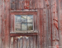 A small window in the wall of an old barn