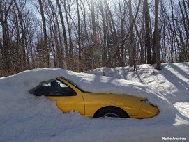 yellow car emerging from snow