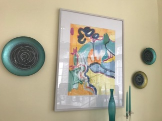 This is the full vignette mixing artwork and plates on my dining room wall