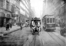 Horses and trolleys share the street with separate sidewalk for pedestrians